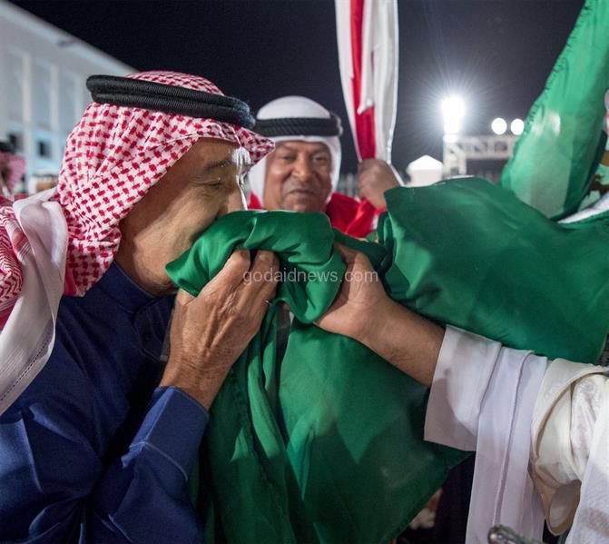 خادم الحرمين الشريفين يقبل العلم البحريني ويتبعه بتقبيل السعودي.. في لقطة تجسد الإخاء بين الأشقاء